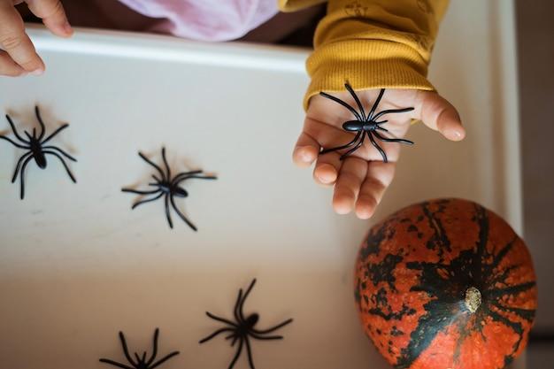 Mains D'un Enfant Jouant Avec Des Jouets D'araignées De Caoutchouc Noir. Halloween Photo Premium
