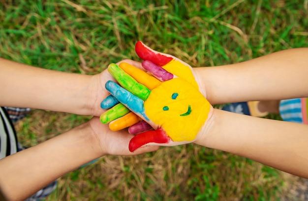 Mains d'enfants en couleurs. photo d'été. mise au point sélective. Photo Premium