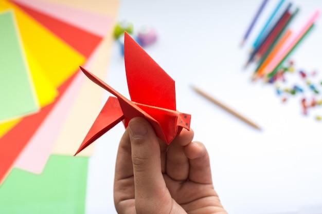 Les mains des enfants font un oiseau origami en papier rouge Photo Premium