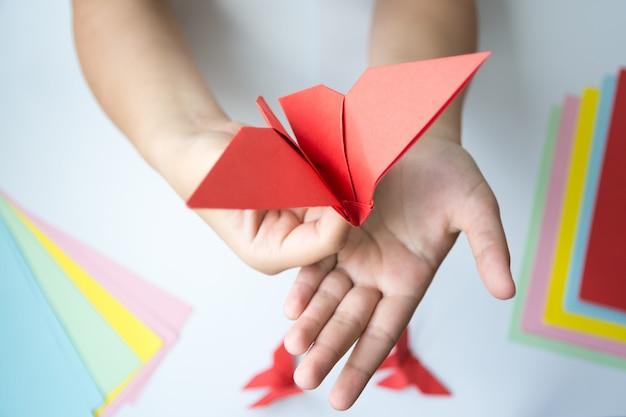 Les mains des enfants font un papillon origami en papier rouge. Photo Premium