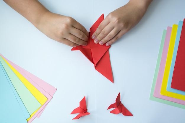 Les mains des enfants font un papillon origami. Photo Premium