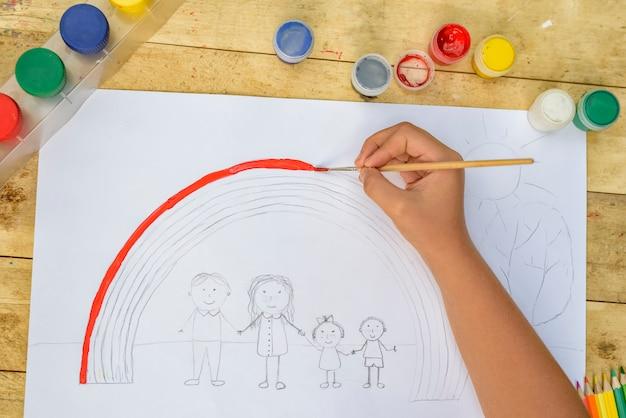 Les mains des enfants peignent un dessin avec un pinceau et de la peinture. vue de dessus Photo Premium