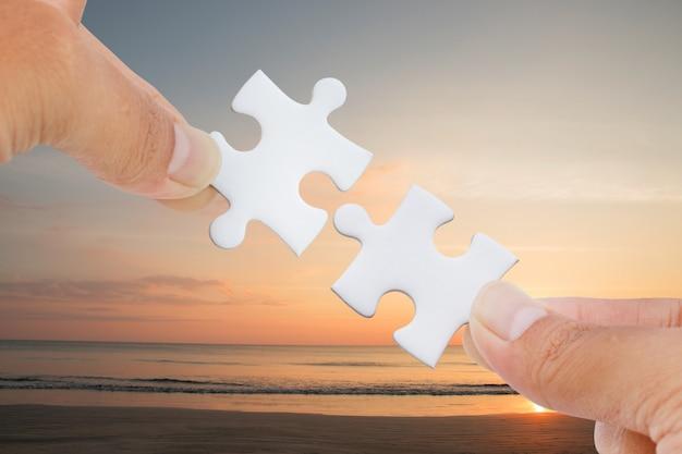 Mains essayant de connecter la pièce de puzzle à la mer et à la plage. Photo Premium