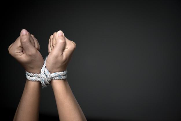 Les mains étaient attachées avec une corde. violence, terrifié, concept de la journée des droits de l'homme. Photo Premium