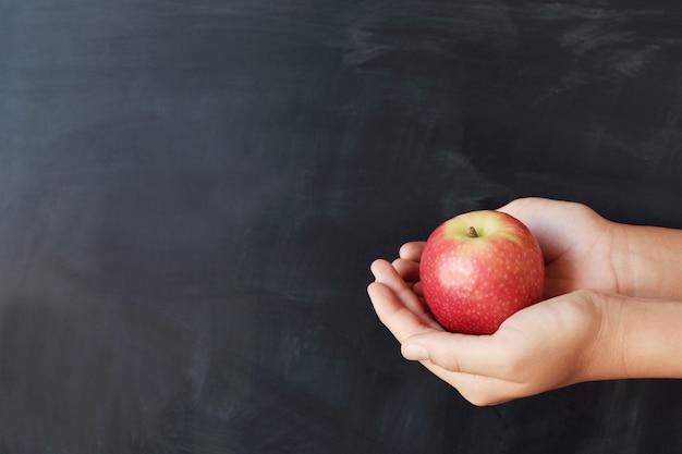 Mains d'étudiant sur pomme rouge avec fond de tableau noir Photo Premium