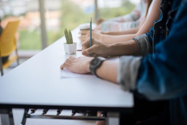 Mains, étudiants, assis, lecture, avoir, examen, tenue, crayon, écriture, papier, feuille-réponse Photo Premium