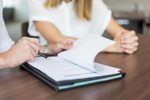 Mains d'un exécutif masculin montrant un contrat avec une partenaire féminine lors d'une réunion. Photo gratuit