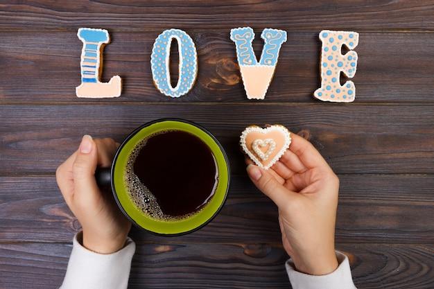 Mains féminines avec café et biscuits en forme de coeur sur la table en bois Photo Premium