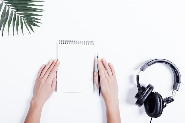 Mains féminines avec un cahier et un crayon, des écouteurs et des plantes sur un tableau blanc Photo Premium