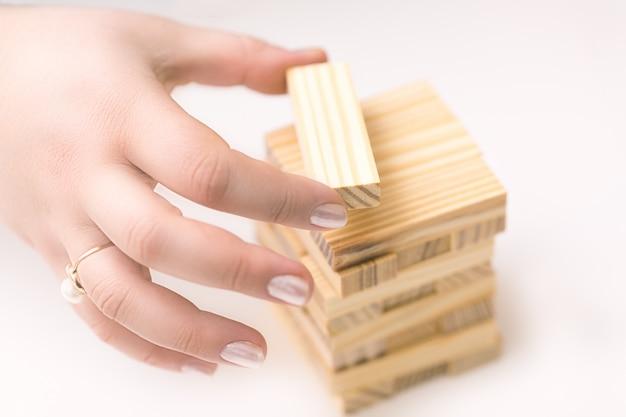 Mains féminines construisant une petite maison de tour en bois à partir d'un bloc wodden pour enfants. Photo Premium