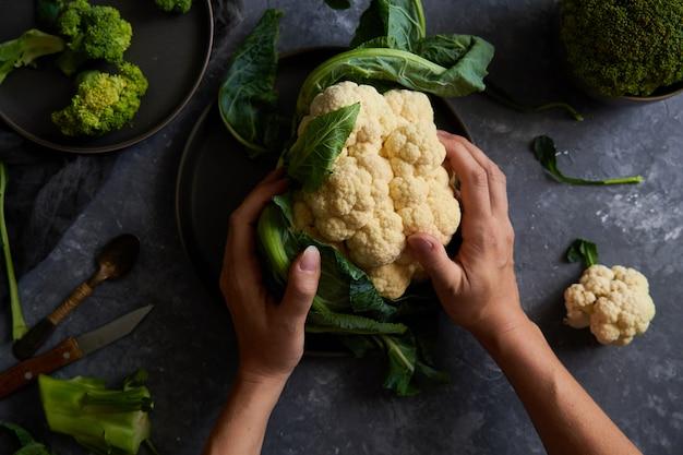 Des mains féminines coupent le chou-fleur et le brocoli sur une assiette Photo Premium