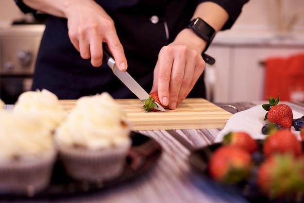 Mains Féminines Avec Un Couteau Coupé Des Fraises Sur Une Planche à Découper Sur La Table De La Cuisine. Cuisson Des Petits Gâteaux Avec Des Fraises Et Des Bleuets. Photo Premium