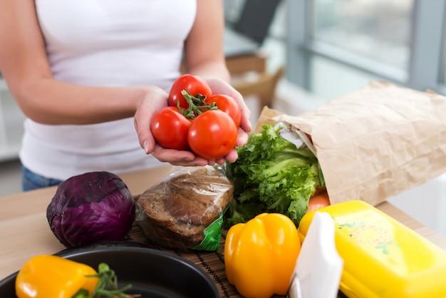 Mains Féminines D'un Cuisinier Caucasien Tenant Un Bouquet De Tomates Rouges Sur Le Plan De Travail De La Cuisine Avec De L'épicerie Fraîche Et Du Pain De Seigle Dessus. Photo Premium