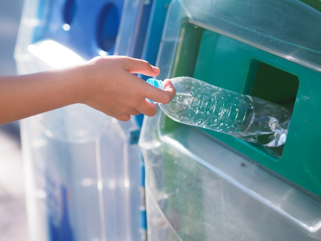 Des mains féminines déposent la bouteille en plastique à la poubelle. Photo Premium