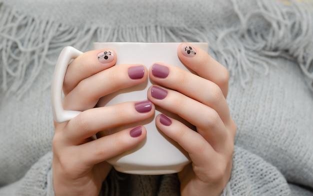 Mains féminines avec un design ongles rose foncé Photo Premium