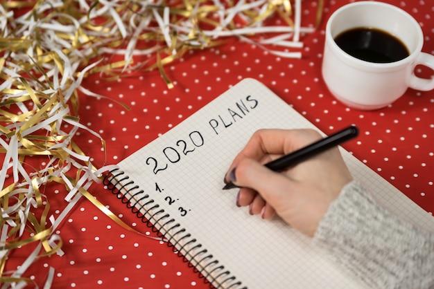 Mains féminines écrivant des plans dans un cahier. Photo Premium