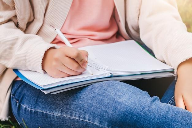 Des Mains Féminines écrivent Dans Un Cahier. Photo Premium