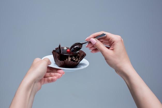 Mains Féminines Gardant Le Gâteau Avec Une Cuillère Sur Fond Gris Photo gratuit