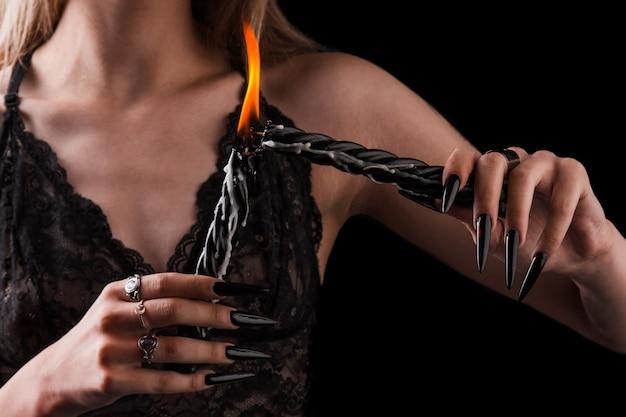 Des mains féminines avec de longs ongles tiennent des bougies allumées, la sorcellerie sur halloween. Photo Premium