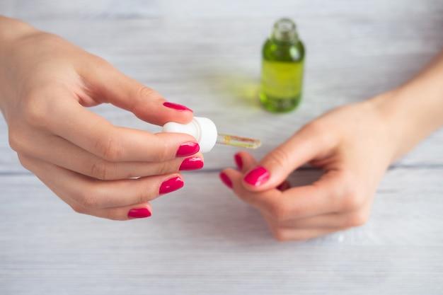 Mains féminines avec manucure rose appliquée huile cosmétique sur les doigts Photo Premium