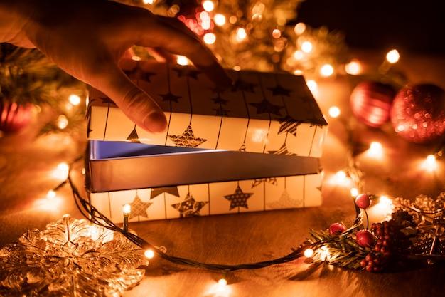 Mains Féminines Ouvrant La Boîte-cadeau De Noël Au-dessus D'une Table En Bois Photo Premium
