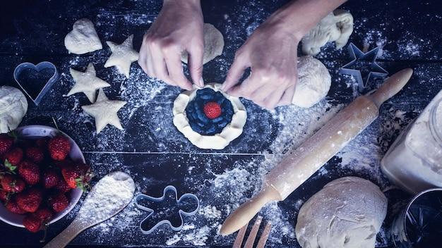 Des mains féminines préparent un gâteau de pâte maison avec une farce de fraise mûre et de baies juteuses de chèvrefeuille Photo Premium