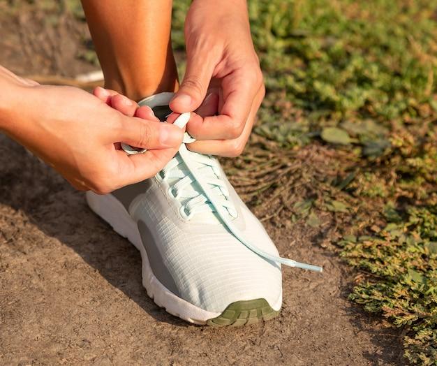 Mains féminines tapant des chaussures de sport en plein air avant de faire du jogging Photo Premium