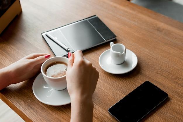 Mains féminines avec un téléphone noir, une tasse de café, une table, un ordinateur portable Photo Premium