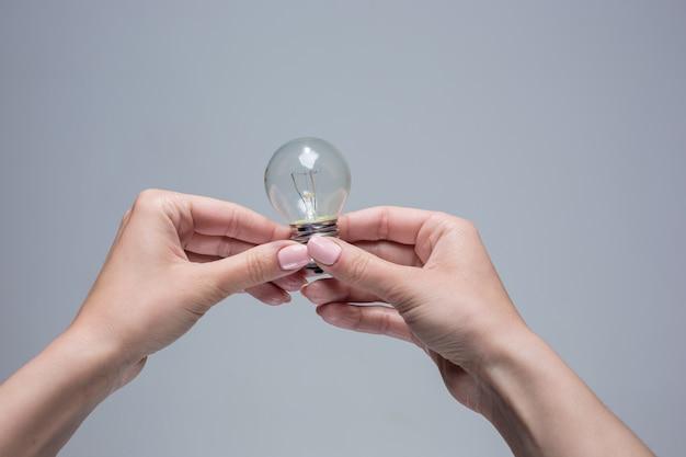 Les Mains Féminines Tenant Une Ampoule à Incandescence Sur Gris Photo gratuit