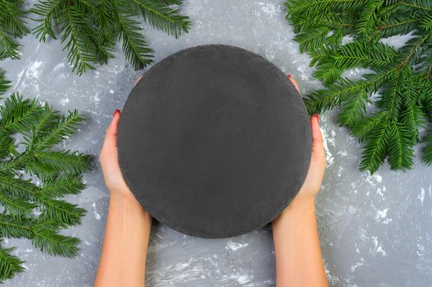 Mains Féminines Tenant Une Assiette En Pierre D'ardoise Noire Vide Avec Des Branches De Noël. Vue D'en-haut Photo Premium