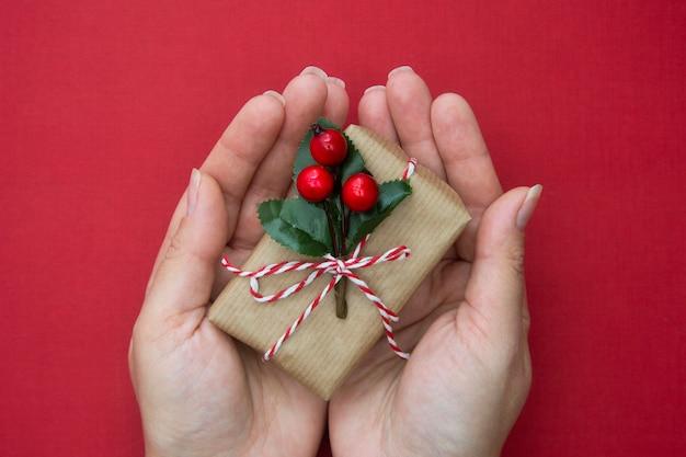 Mains féminines tenant une boîte de cadeau de noël avec ruban rouge, sur fond rouge. Photo Premium
