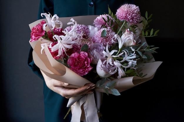 Mains féminines tenant un bouquet décoré dans un style vintage sur un fond sombre Photo Premium