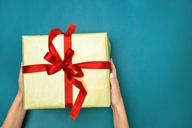Les Mains Féminines Tenant Un Cadeau Sur Fond Bleu Photo gratuit