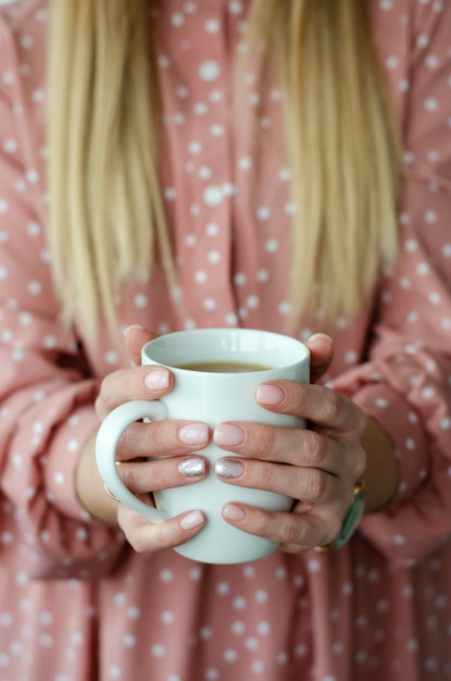 Mains féminines tenant une tasse blanche avec boisson. fermer. arrière-plan flou Photo Premium