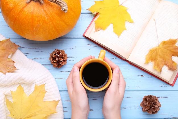 Mains féminines tenant une tasse de café noir avec des feuilles d'automne Photo Premium