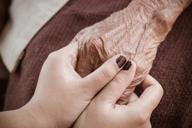 Mains de femme adolescente asiatique tenant des mains de grand-mère âgée ridée Photo Premium
