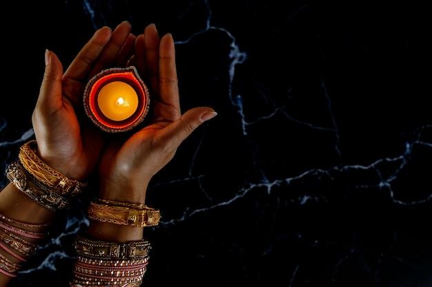 Les Mains De La Femme Au Henné Tenant Une Bougie Allumée Pour Le Festival De Diwali Photo Premium