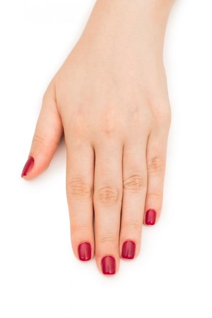 Mains femme avec clou rouge isolé on white Photo Premium