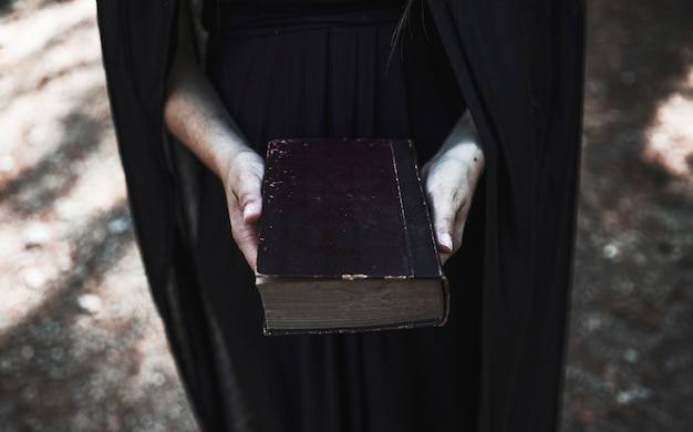 Mains, de, femme, dans, robe noire, tenue, vieux livre Photo gratuit