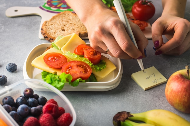 Mains de femme écrivent une note 'avec amour' près de sandwich aux légumes et au fromage sur fond gris Photo Premium