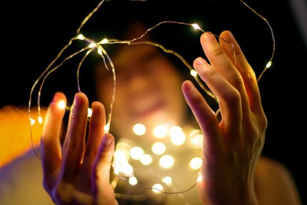 Mains De Femme Heureuse Tenant La Lumière De Noël Jaune, Fond De Bokeh Photo Premium