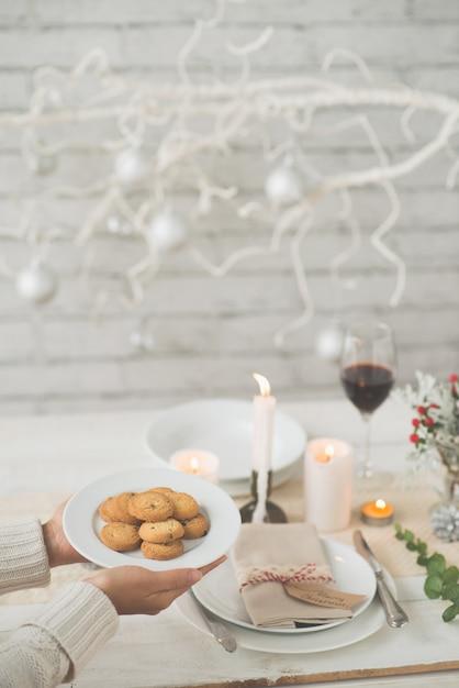 Mains de femme méconnaissable portant une assiette de biscuits à la table du dîner de noël Photo gratuit