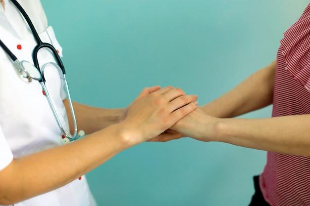 Les mains de la femme médecin tiennent la main du patient pour l'encouragement et l'empathie. partenariat, confiance et concept d'éthique médicale. Photo Premium