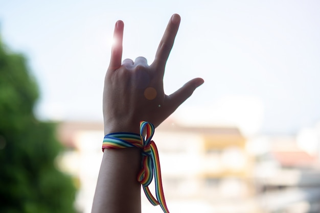 Mains de femme montrant un signe d'amour avec ruban lgbtq rainbow Photo Premium