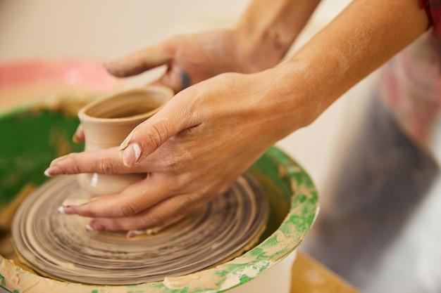 Les Mains D'une Femme Moulent Un Vase Sur Un Cercle Photo gratuit