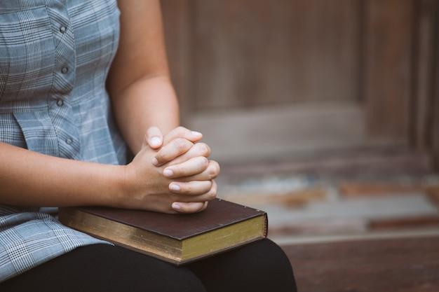 Mains De Femme Plié En Prière Sur Une Sainte Bible Pour Le Concept De La Foi Dans Le Ton De Couleur Vintage Photo Premium