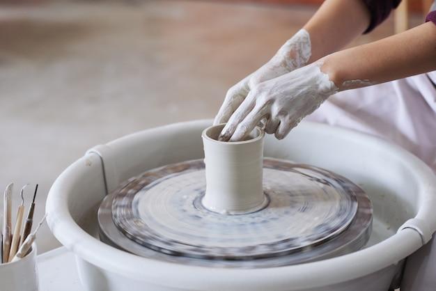 Mains de femme potier non reconnaissable confectionnant un vase en terre cuite sur un tour de potier Photo gratuit