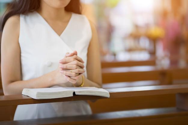 Mains de femme priant sur une sainte bible dans l'église pour le concept de la foi, la spiritualité et la religion chrétienne Photo Premium