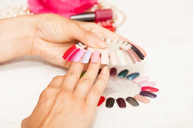Mains d'une femme qui choisit la couleur de son vernis à ongles Photo Premium