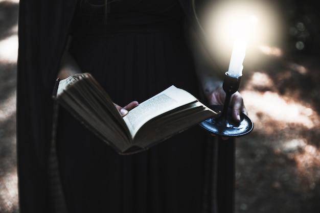 Mains de femme en robe noire tenant livre ouvert et bougie allumée Photo gratuit